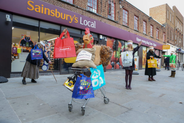 Person in a chicken suit sat in a trolly with 'GM chicken feed' and supermarket shopping bags, outside a Sainsbury's with blindfolded shoppers behind © Matt Writtle 2016