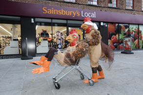 Person in a chicken suit sat in a trolly being pushed by another chicken wearing a blindfold, outside a Sainsbury's © Matt Writtle 2016