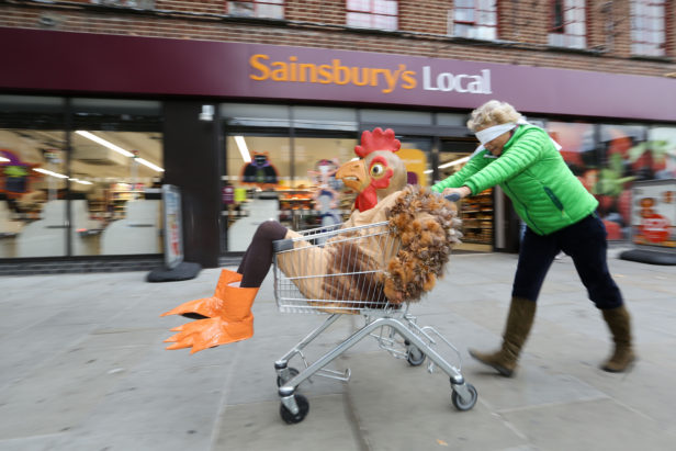 Person in a chicken suit sat in a trolly being pushed by a blindfolded shopper, outside a Sainsbury's © Matt Writtle